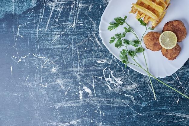 Gebakken aardappelen met cotlets en citroen. Gratis Foto