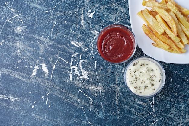 Gebakken aardappelen met ketchup en mayonaise. Gratis Foto