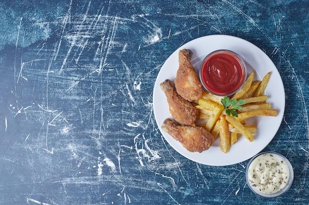Gebakken aardappelen met kippenpoten en sauzen. Gratis Foto
