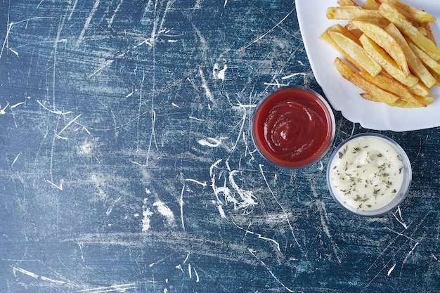 Gebakken aardappelen met mayonaise en ketchup. Gratis Foto