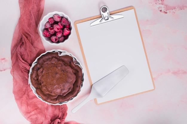 Gebakken cake; framboos; spatel op klembord met witboek over de roze gestructureerde achtergrond Gratis Foto