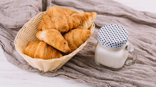 Gebakken croissants en melk in gesloten metselaarkruik op verfrommelde zaktextiel Gratis Foto