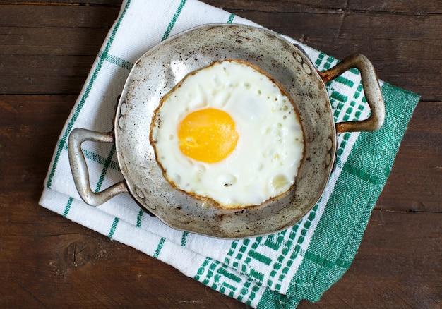 Gebakken ei in een oude koekenpan op servet Premium Foto