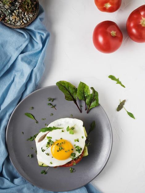 Gebakken ei met tomaten en bladeren van rucola en tijm op brood in een grijze plaat Gratis Foto