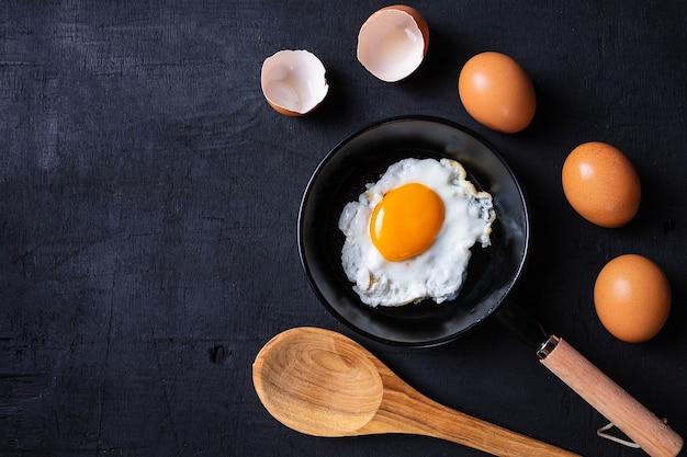 Gebakken eieren in een koekenpan en eierschaal voor het ontbijt op een zwarte achtergrond. Premium Foto