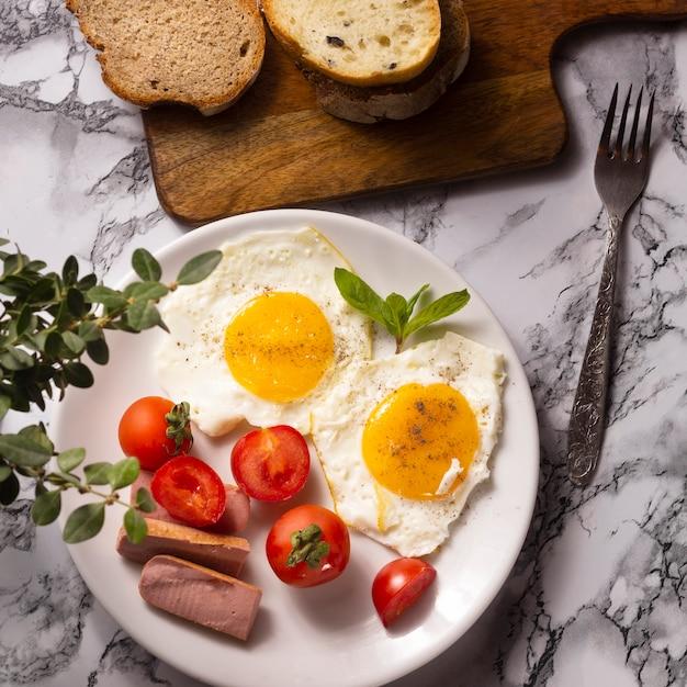 Gebakken eieren met cherrytomaten en hotdogs Gratis Foto