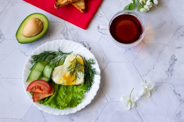 Gebakken eieren met sla, komkommer en tomatenplakken op een lichte achtergrond Premium Foto
