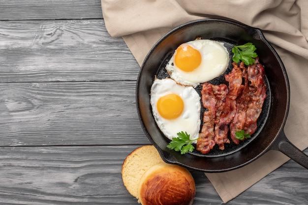 Gebakken eieren met spek in een pan. bovenaanzicht Premium Foto