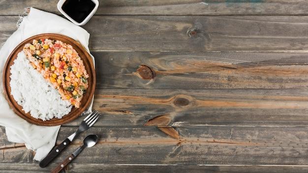 Gebakken en gestoomde rijst op houten plaat met vork en lepel over de tafel Gratis Foto