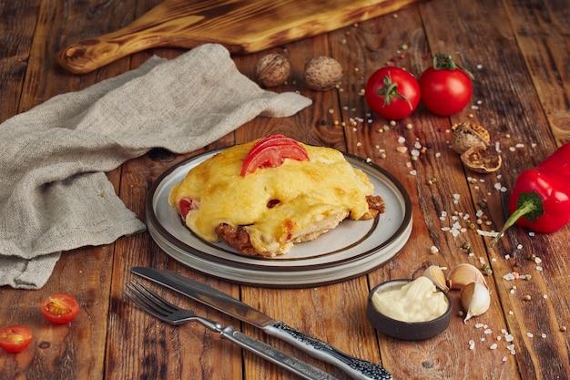 Gebakken frans vlees met kaas en champignons op houten tafel Premium Foto