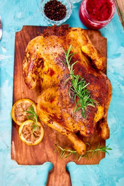 Gebakken hele kip met sauzen op houten bord op blauwe achtergrond. Premium Foto