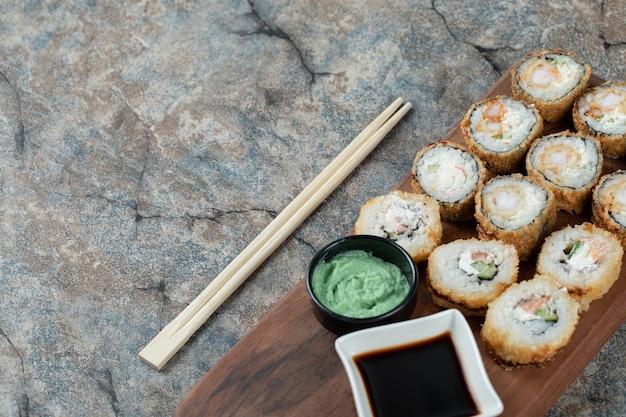 Gebakken hete sushi rolt met roomkaas, wasabi en sojasaus op een houten bord. Gratis Foto