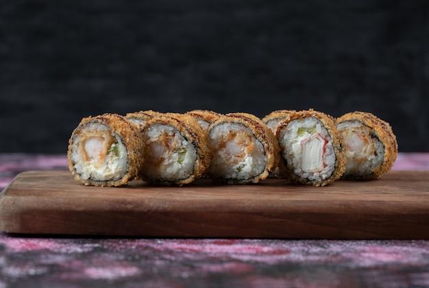 Gebakken hete sushi rolt op een houten bord. Gratis Foto