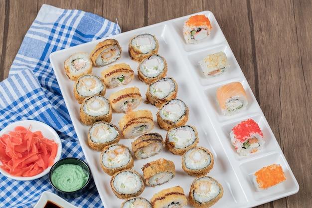 Gebakken hete sushibroodjes met sojasaus, wasabi en gember op een blauw geruite handdoek. Gratis Foto