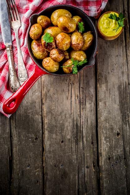 Gebakken in pan hele jonge aardappelen, zelfgemaakte vegetarische gerechten, houten oude rustieke tafel, met saus, hierboven Premium Foto