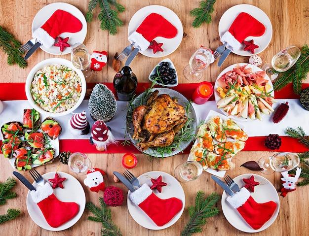 Gebakken kalkoen. kerstdiner. de kersttafel wordt geserveerd met een kalkoen, versierd met helder klatergoud en kaarsen. gebakken kip, tafel. familie diner. bovenaanzicht, plat, overhead, kopieerruimte Gratis Foto