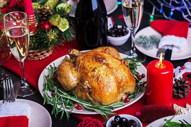 Gebakken kalkoen. kerstdiner. de kersttafel wordt geserveerd met een kalkoen, versierd met helder klatergoud en kaarsen. gebakken kip, tafel. familie diner. Gratis Foto