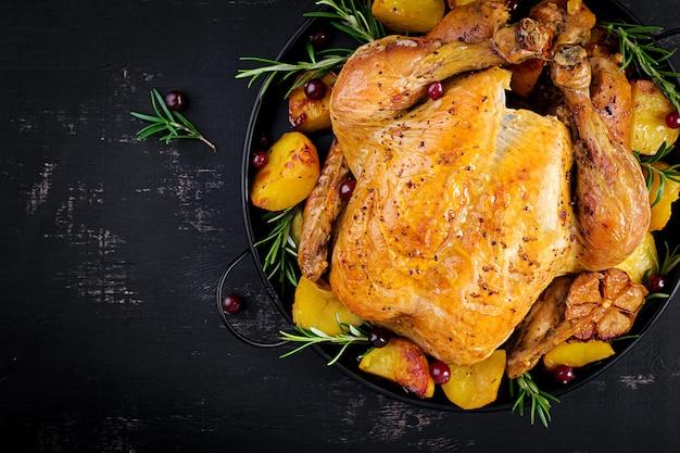 Gebakken kalkoen of kip. de kersttafel wordt geserveerd met een kalkoen, versierd met helder klatergoud. gefrituurde kip. tafel opstelling. kerstdiner. bovenaanzicht Premium Foto