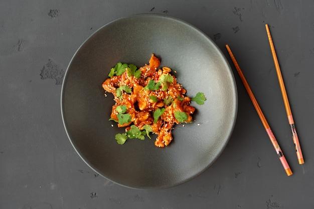Gebakken kip en pinda's met saus in zwarte keramische kom bovenaanzicht, grijze achtergrond Premium Foto