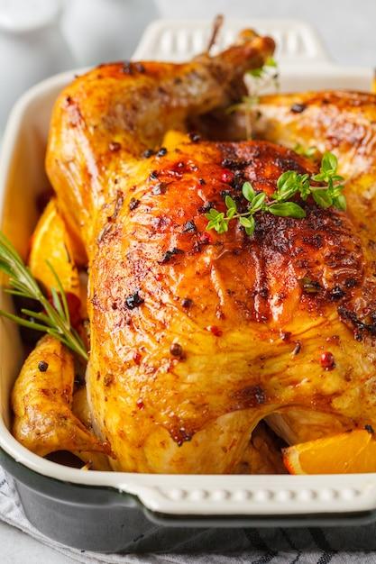 Gebakken kip met kruiden, veenbessen, sinaasappel en uien in een glazen schaal. Premium Foto