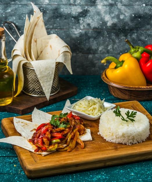 Gebakken kip met paprika geserveerd met rijst en geraspte kaas Gratis Foto