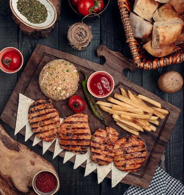 Gebakken kipfilet met patat en rijst bovenaanzicht Gratis Foto