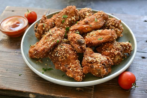Gebakken kippenvleugels met sesamzaadjes. ketchup en chilisaus. vrije ruimte voor tekst. houten tafel. heerlijke gebakken kippenvleugels. detailopname Premium Foto