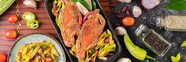 Gebakken krab met kerriepoeder in een bord met paprika en tomaten. Gratis Foto