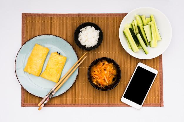 Gebakken loempia's; salade; gekookte rijst en gesneden courgette met mobiele telefoon over placemat Gratis Foto