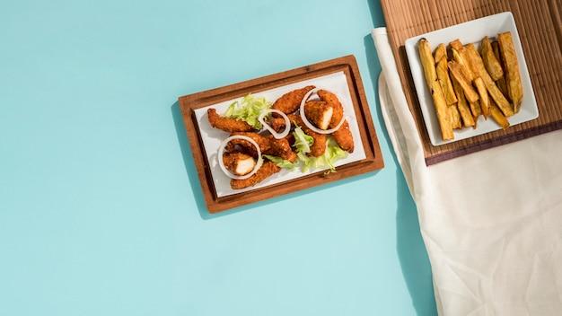 Gebakken nuggets met groen en gesneden aardappelen Gratis Foto