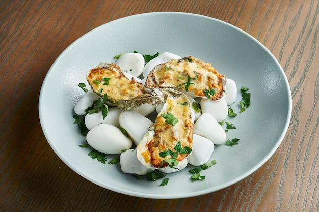 Gebakken oesters met kaas op zee, hete stenen. gezonde zeevruchten. filmeffect tijdens post. Premium Foto