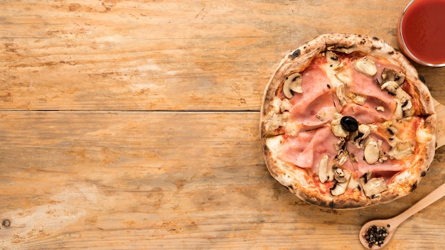 Gebakken paddestoel en baconpizza met tomatensaus over oude houten lijst Gratis Foto