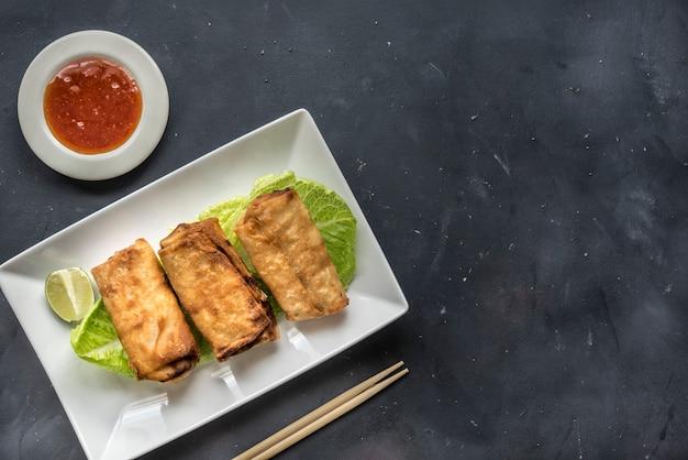 Gebakken plantaardige loempia's met verse ingrediënten geserveerd en zure saus in een oosters restaurant Premium Foto