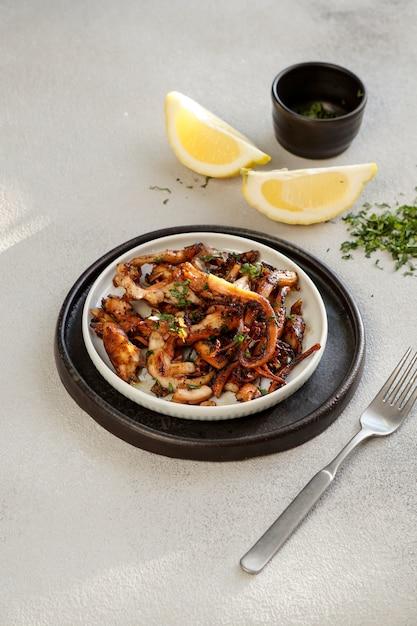 Gebakken stukjes octopus met citroen, pulpo frito, fel zonlicht Premium Foto