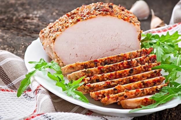 Gebakken varkensvlees versierd met rucola bladeren Gratis Foto