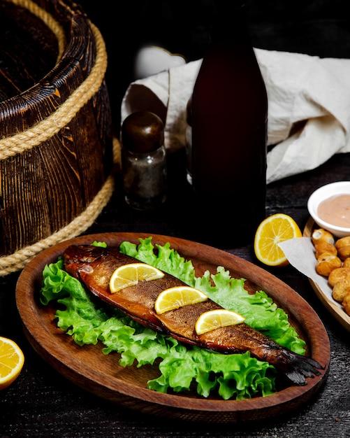 Gebakken vis met plakjes citroen op de tafel Gratis Foto
