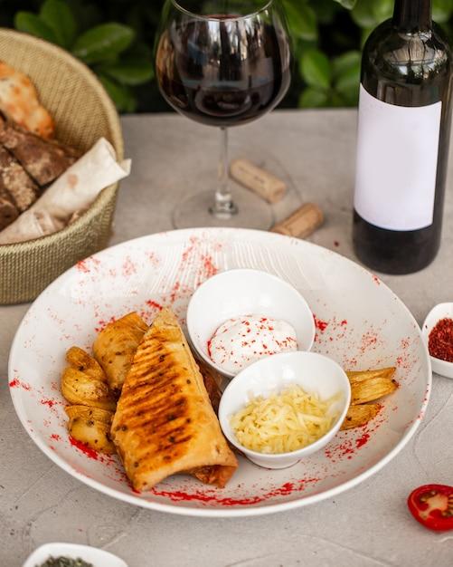 Gebakken wraps geserveerd met aardappel, geraspte kaas en mayonaise Gratis Foto
