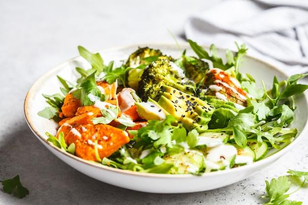 Gebakken zoete aardappel, broccoli en avocado slakom met tahin dressing. Premium Foto