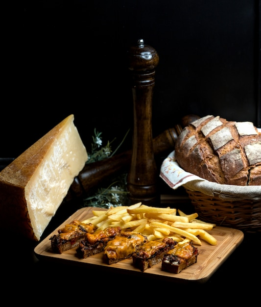 Gebakken zwart brood met uien en vlees gegarneerd met geraspte kaas Gratis Foto
