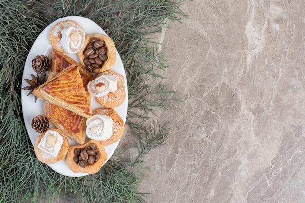Gebaksschotel met koekjes, turkse lekkernijen en kyata's op dennenbladeren op marmer. Gratis Foto
