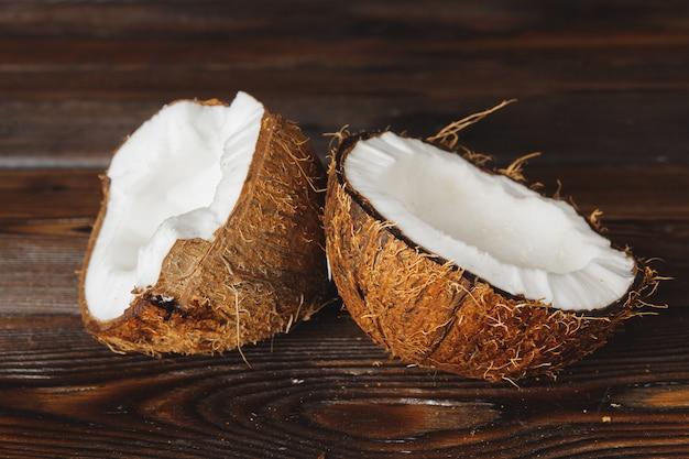 Gebarsten kokosnootstukken op donkere houten achtergrond Premium Foto