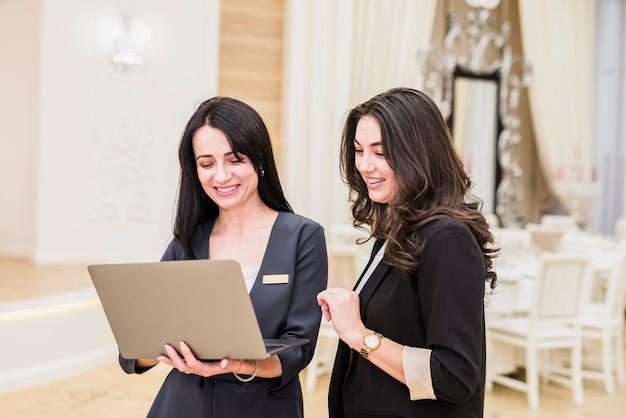 Gebeurtenismanager die laptop tonen aan gelukkige vrouw Gratis Foto