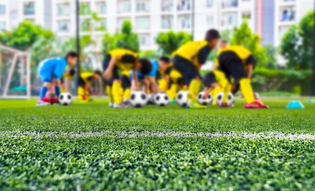 Gebiedsvoetbal in achtergrondjonge geitjesvoetbalsters die op hoogte opleiden Premium Foto