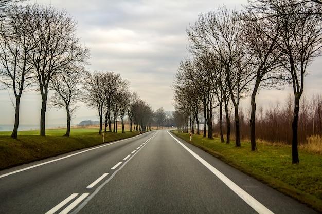 Gebogen two lane country road kronkelende door bomen. Premium Foto