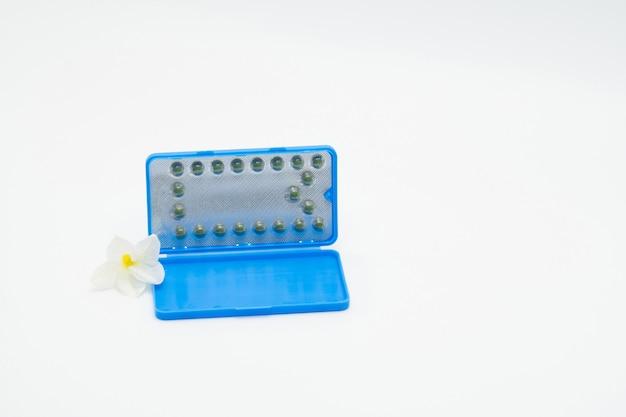 Geboortenbeperkingspillen of contraceptieve pil met document geval en witte bloem op witte achtergrond. gezinsplanning concept. hormoonvervangingstherapie. hormonale acnebehandeling met anti-androgene pil. Premium Foto
