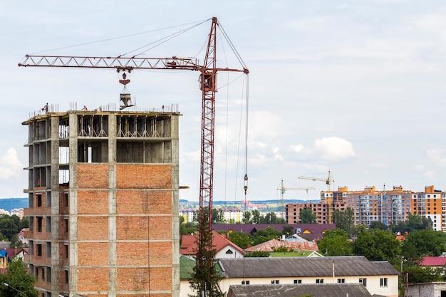 Gebouw met hoge verdiepingen in aanbouw met torenkraan en arbeidersmensen Premium Foto