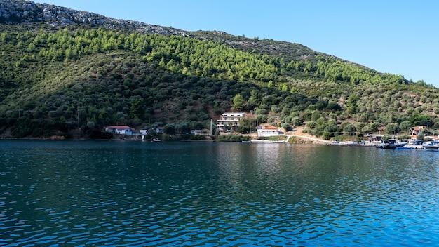 Gebouwen en afgemeerde boten aan het water, veel groen, groene heuvels, griekenland Gratis Foto