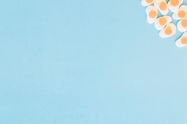 Gebraden kleverig eisuikergoed op de hoek van blauwe achtergrond Gratis Foto