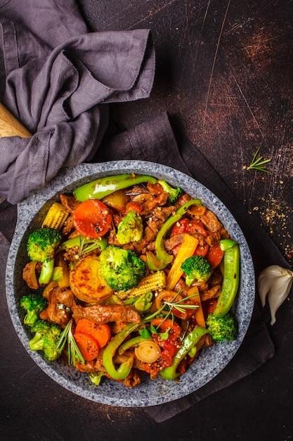 Gebraden rundvleesstroganoff met aardappels en groenten in een pan, hoogste mening. Premium Foto