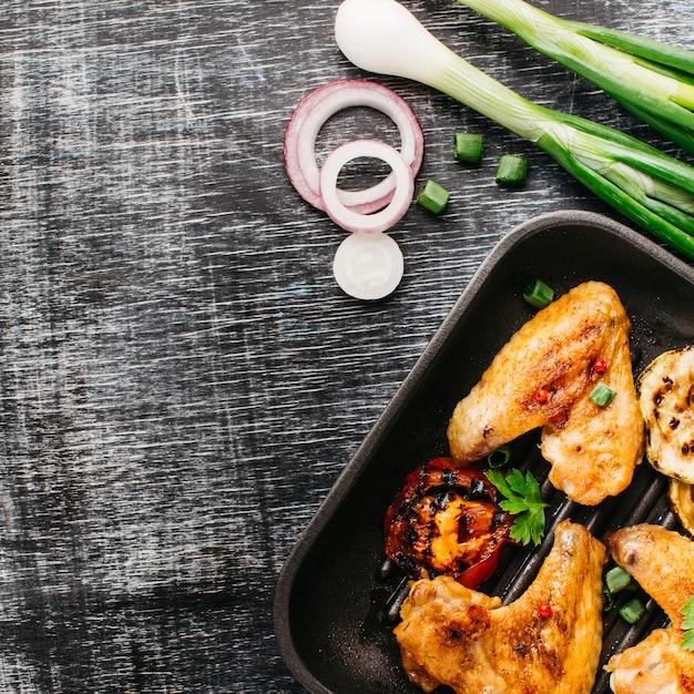 Gebraden smakelijk vlees in gebraden gerechtpan met ui op houten lijst Gratis Foto
